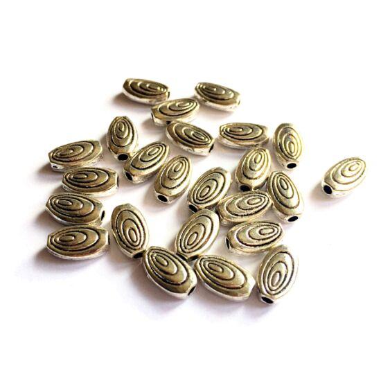 Fém köztes gyöngy- ovális formában, csiga motívum díszítéssel -antik ezüst színeben