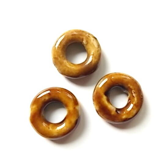 Foltos barna színű, lyukas korong alakú, kerámia gyöngy